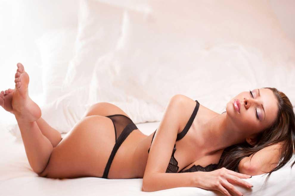Женщина лежит на кровати в нижнем кружевном белье